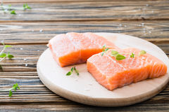 Raw uncooked salmon on cutting board on wooden table. Two pieces of fillet of raw uncooked salmon on cutting board garnished with fresh thyme on wooden table Royalty Free Stock Photo