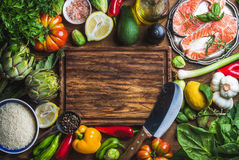 Raw uncooked salmon fish with vegetables, rice, herbs, spices and wine on chopping board over rustic wooden background Royalty Free Stock Photography