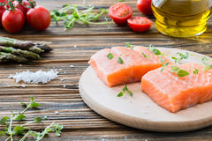 Raw uncooked salmon and vegetables on wooden table. Two pieces of fillet of raw uncooked salmon on cutting board garnished with fresh thyme, asparagus, cherry Royalty Free Stock Photography