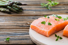 Raw uncooked salmon and vegetables on wooden table. Two pieces of fillet of raw uncooked salmon on cutting board garnished with fresh thyme, asparagus on wooden Stock Images