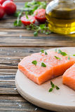 Raw uncooked salmon and vegetables on wooden table. Two pieces of fillet of raw uncooked salmon on cutting board garnished with fresh thyme, cherry tomatoes Royalty Free Stock Photos