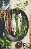 Raw uncooked sea bass fish with herbs and asparagus. Cooking fish dinner. Flat-lay of raw uncooked sea bass fish with fresh herbs and vegetables on dark plate stock images