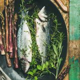 Raw uncooked sea bass fish with herbs, square crop. Cooking fish dinner. Flat-lay of raw uncooked sea bass fish with herbs and vegetables over rustic wooden stock photography