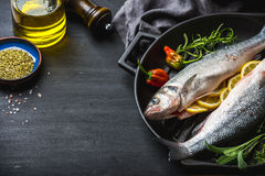 Raw uncooked seabass fish with herbs and spices in cast iron cooking pan on black wooden background Royalty Free Stock Image