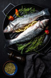 Raw uncooked seabass fish with herbs and spices in cast iron cooking pan on black wooden background Stock Photos