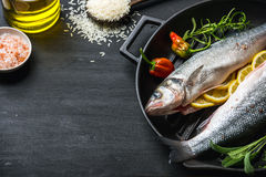 Raw uncooked seabass fish with herbs, spices and rice in cast iron cooking pan on black wooden background Royalty Free Stock Photo