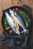 Raw uncooked seabass fish with lemon slices, herbs and spices on black grilling iron pan over rustic wooden background Royalty Free Stock Images