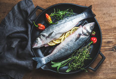 Raw uncooked seabass fish with lemon slices, herbs and spices on black grilling iron pan over rustic wooden background Stock Photography