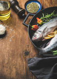 Raw uncooked seabass fish with rice, olive oil, lemon slices, herbs and spices on black grilling iron pan over rustic Stock Images