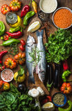 Raw uncooked seabass fish, vegetables, grains, herbs, rice spices and olive oil on rustic wooden chopping board, top Stock Photography