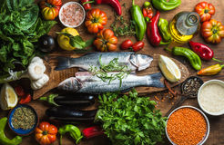 Raw uncooked seabass fish with vegetables, grains, herbs and spices on chopping board over rustic wooden background Stock Image