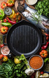 Raw uncooked seabass fish, vegetables, grains, herbs, spices and olive oil on chopping board, iron grilling pan in Stock Images