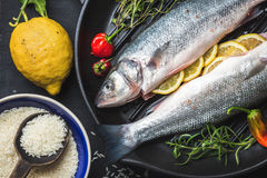 Raw uncooked seabass with rice, lemon, herbs and spices on black grilling iron pan over dark background Royalty Free Stock Photo