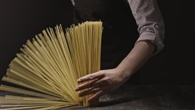 Woman`s hand holds a bunch of italian pasta on a dark background. Slow motion, Full HD video, 240fps, 1080p. Raw uncooked spaghetti falling in slow motion from stock video footage