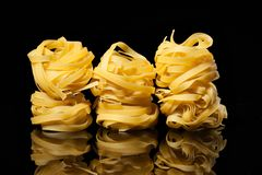 Raw uncooked tagliatelle nests on black background with reflection. Traditional Italian pasta. Raw uncooked tagliatelle nests on the black background with royalty free stock photography