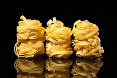 Raw uncooked tagliatelle nests on black background with reflection. Traditional Italian pasta. Raw uncooked tagliatelle nests on the black background with stock images