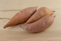 Raw uncooked yams. Three raw uncooked whole yams on wooden table Stock Photo