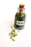 Raw uncut Peridot gem stones in bottle Stock Image