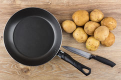 Raw unpeeled potatoes, frying pan and knife on wooden table Stock Photography