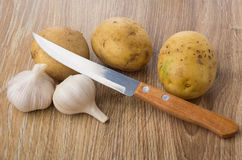 Raw unpeeled potatoes, garlic and kitchen knife on table Stock Image