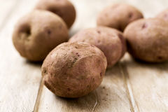 Raw unpeeled potatoes on a table. Some raw unpeeled potatoes on a white rustic wooden table stock photography