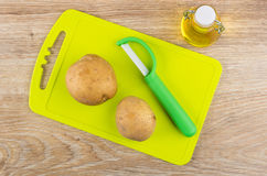 Raw unpeeled potatoes, vegetable peeler on cutting board and oil Stock Images