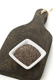 Raw unprocessed black chia seeds in small white bowl on wooden b Stock Photo