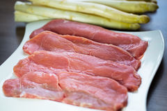 Raw veal chops with white asparagus in the background. Diet Stock Photos