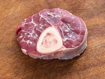 Raw veal meat with marrow bone on cutting board royalty free stock images