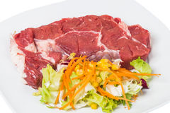 Raw veal and salad. Raw meat and salad isolated on white background Royalty Free Stock Photography