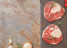 Raw veal shank meat and ingredients. Raw fresh sliced veal shank and Ingredients for making Osso Buco on rustic background. Overhead view, vintage toned image stock photo
