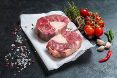 Raw veal shank slices meat. And ingredients for Osso Buco cooking on black background, top view Royalty Free Stock Photo