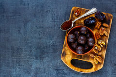 Raw vegan balls. Dates, cocoa and mix nuts sweet delicious raw vegan balls in bowl on vintage board over dark wooden backdrop, top view, copy space. Vegetarian Stock Images