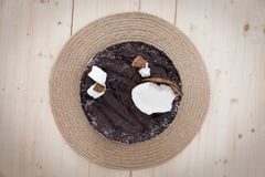 Raw vegan bounty cake. A beautiful raw vegan bounty cake decorated in an exotic shape on a wooden table stock photography