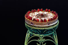 Raw vegan cake decorated with nice colored full fruits, nuts, flower seeds and natural organic ingredients. Healthy and yet tasty Royalty Free Stock Photo
