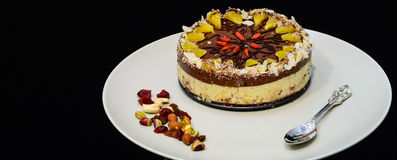 Raw vegan cake decorated with nice colored full fruits, nuts, flower seeds and natural organic ingredients. Healthy and yet tasty Royalty Free Stock Image
