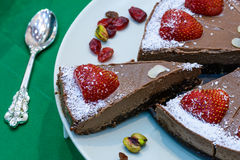 Raw vegan cake decorated with nice colored full fruits, nuts, flower seeds and natural organic ingredients. Healthy and yet tasty Stock Image
