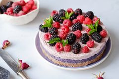 Raw vegan cake with raspberries and bluberries on white table Royalty Free Stock Photos