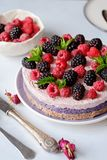 Raw vegan cake with raspberries and bluberries on white table. Raw vegan colorful cake with raspberries and bluberries on white table stock image