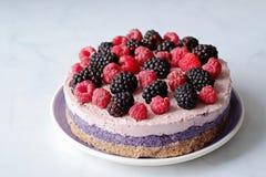 Raw vegan cake with raspberries and bluberries on white table. Raw vegan colorful cake with raspberries and bluberries on white table royalty free stock photo