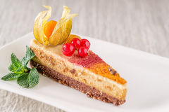 Raw vegan cake with red currants and physalis on the plate, product photography for patisserie, healthy lifestyle Royalty Free Stock Image