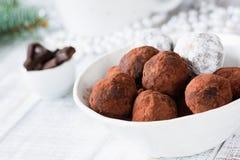 Raw vegan chocolate truffles with dates and raw chocolate. Raw vegan chocolate truffles made with dates and raw chocolate in white bowl. Horizontal view, closeup stock photo