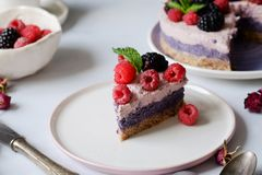 Raw vegan cake with raspberries and bluberries on white table. Raw vegan colorful cake with raspberries and bluberries on white table royalty free stock photos