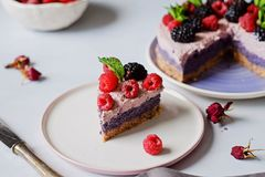 Raw vegan cake with raspberries and bluberries on white table Royalty Free Stock Photography
