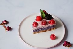 Raw vegan cake with raspberries and bluberries on white table Stock Images