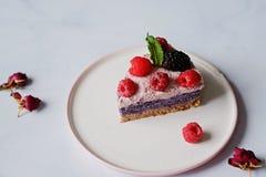 Raw vegan cake with raspberries and bluberries on white table. Raw vegan colorful cake with raspberries and bluberries on white table stock images