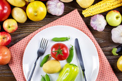 Raw vegan food concept. Raw vegetables, plate with cutlery and napkin on wooden background. Overhead royalty free stock image