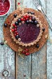 Raw vegan pie with berry jam and organic currants on blue background copyspace. Above view royalty free stock photos