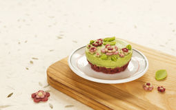 Raw vegan spinach cake with the raw marzipan flowers and leaves Stock Image