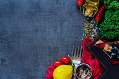 Raw vegetable ingredients. Bio vegetable ingredients for healthy cooking or salad making with kale, lemon and tomatoes on vintage backdrop, top view, copy space Stock Image